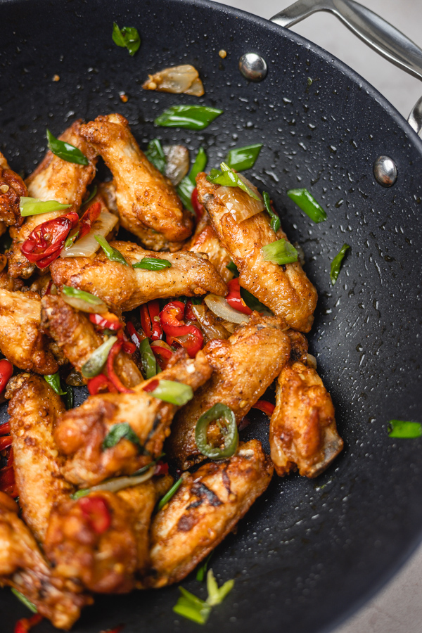 chicken wings and peppers in a wok.