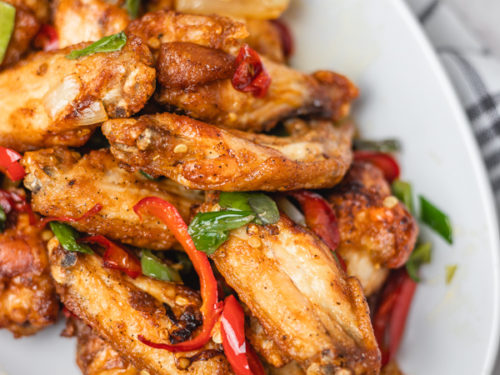 salt and pepper chicken wings on a white plate.