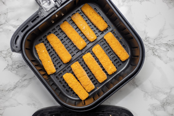 frozen fish in air fryer basket.