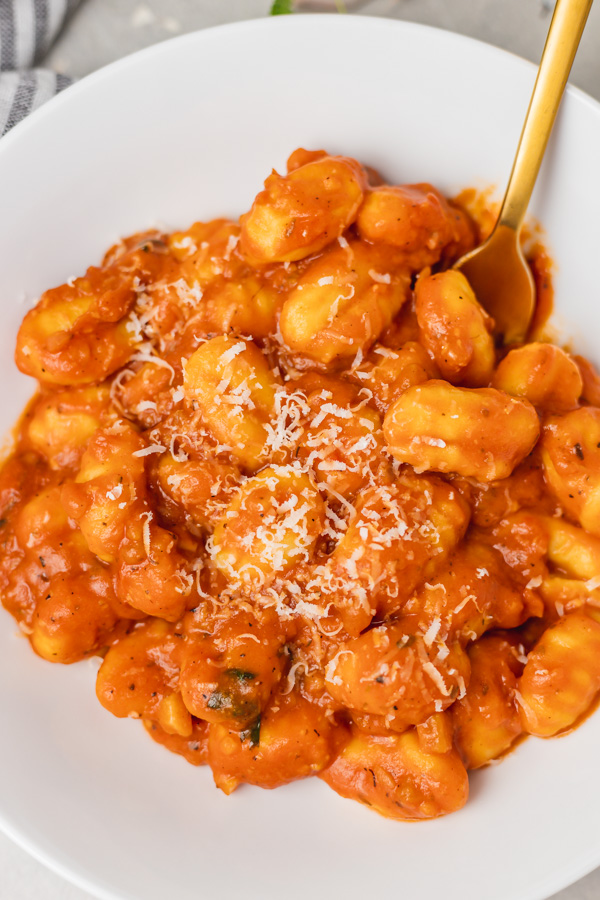 a plate of gnocchi in red sauce topped with parmesan cheese.