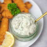 a pot of white sauce with fish sticks and a lemon wedge.