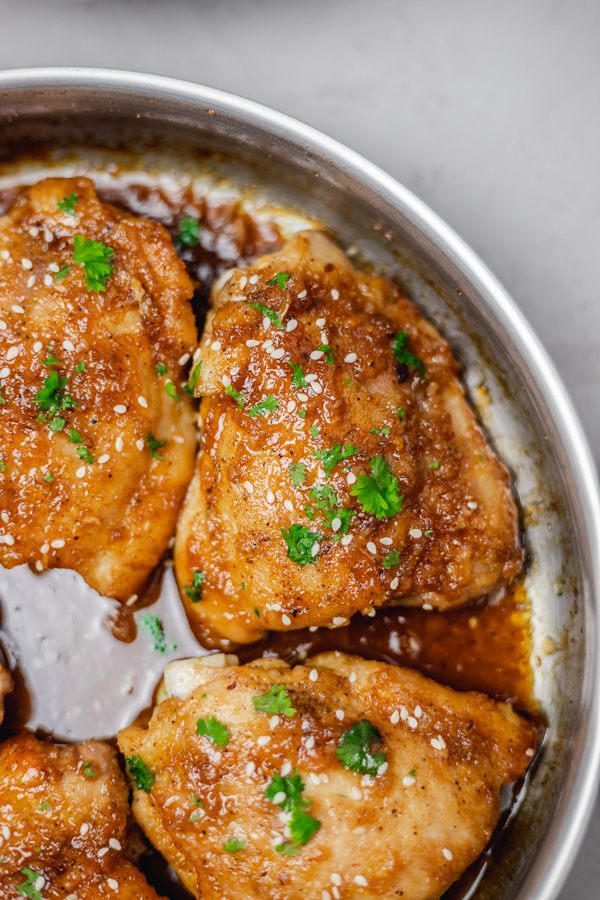 cooked chicken thighs in a pan garnished with sesame seeds and parsley.
