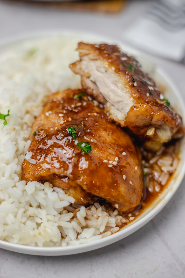 a plate of rice and sticky chicken.