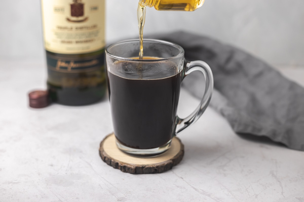 pouring whiskey into coffee.