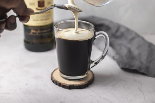 a hand pouring cream at the back of spoon over a cup of coffee.