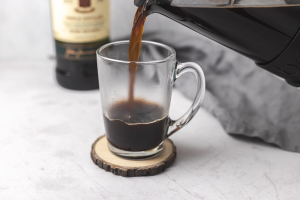 pouring coffee in a glass mug.