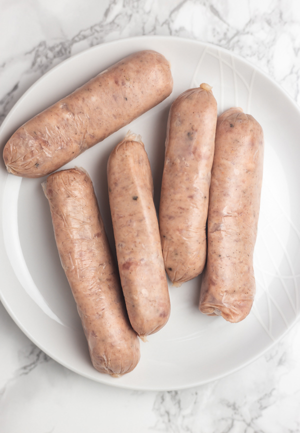 five raw unlinked sausages on a white plate.