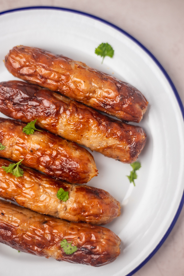 sausages on a white and blue enamel plate.