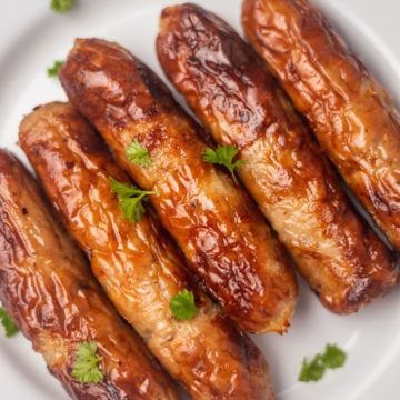 five cooked sausages on a plate.