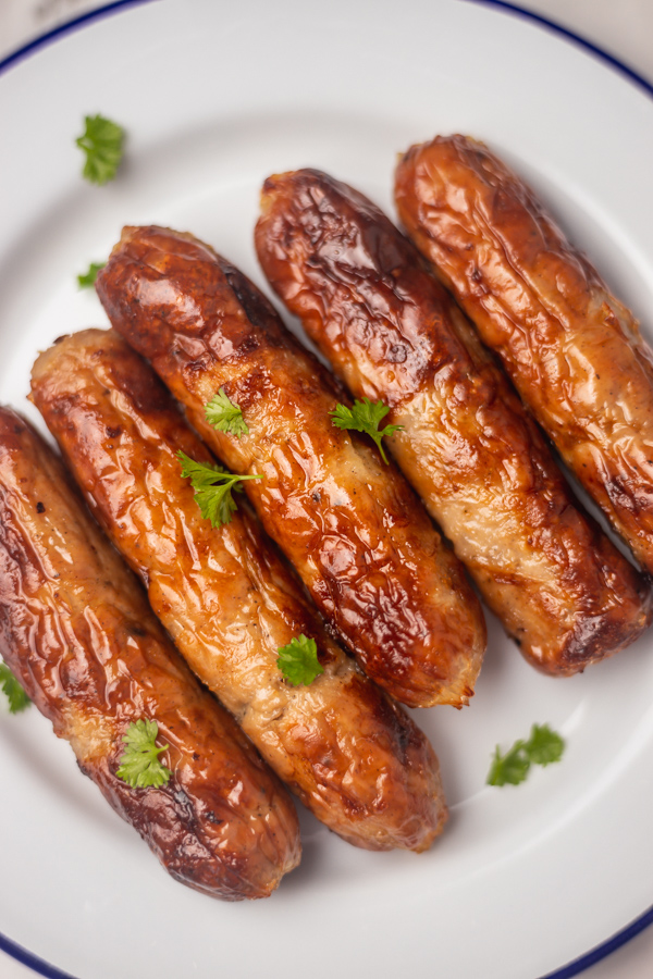 five sausages garnished with chopped parsley on a plate.