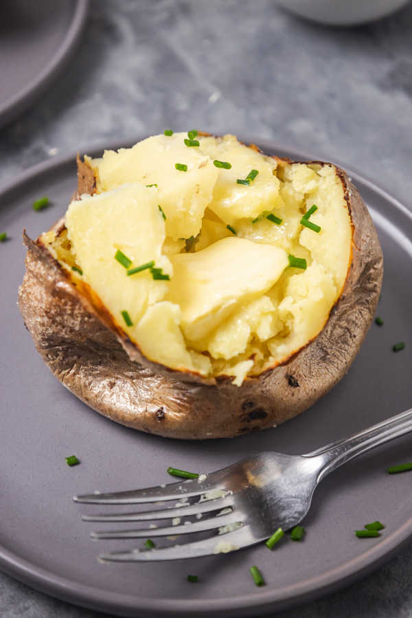 an opened face baked potato on a grey plate with a fork.