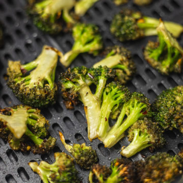 cooked broccoli florets in the air fryer basket.