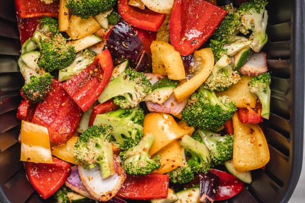 seasoned chopped vegetable medley in an an air fryer basket.