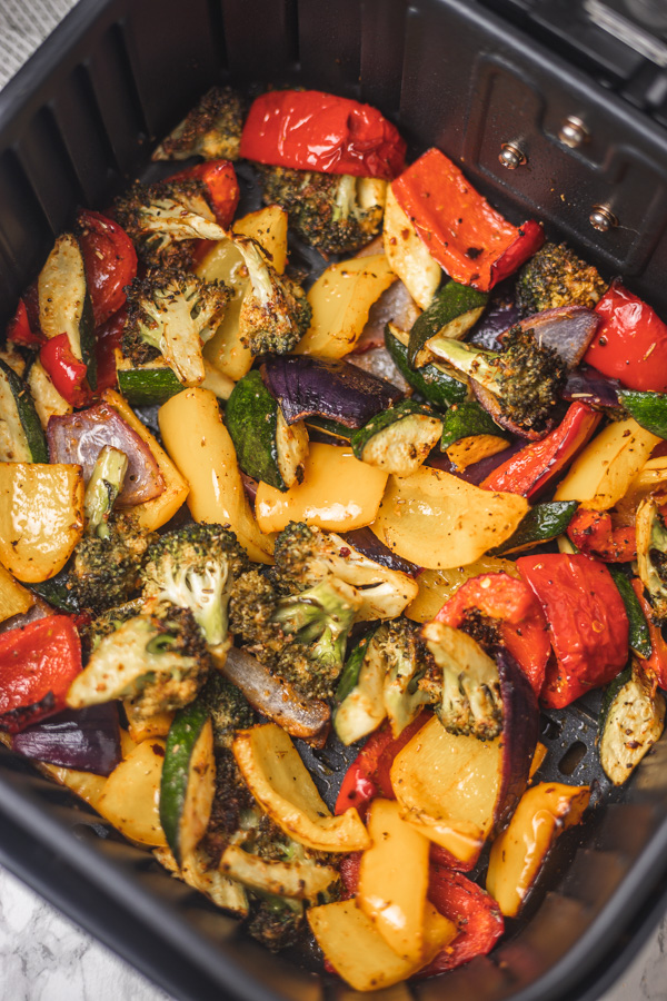 roasted vegetable medley in air fryer basket.