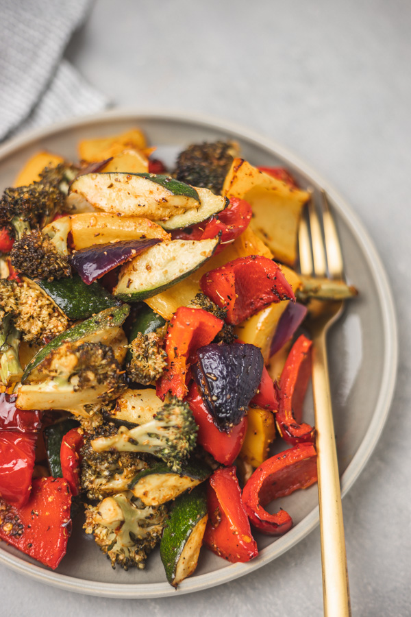 a plate of roasted vegetables with a fork.