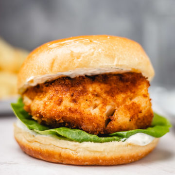 one fish burger on a wooden surface.