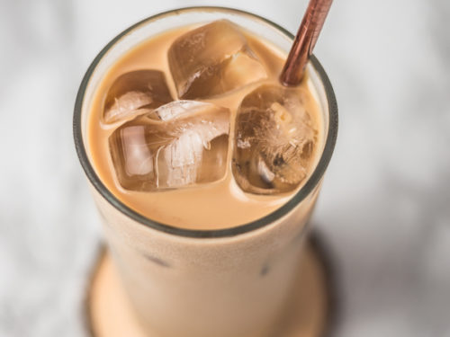 a glass of iced coffee with straw.