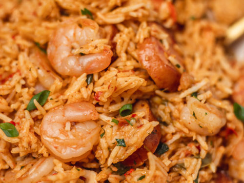 a plate of rice, shrimps and sausages.
