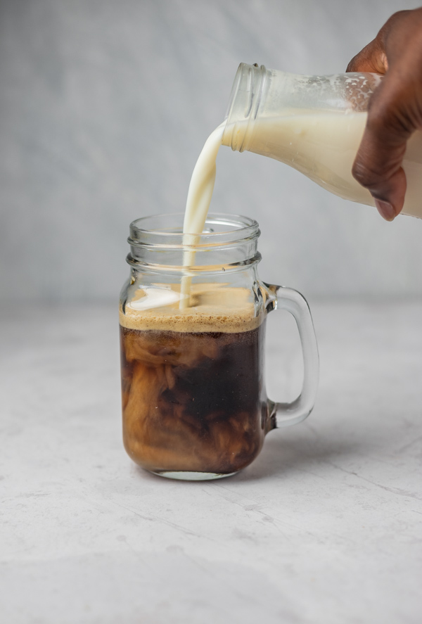A hand pouring milk into a glass of coffee.