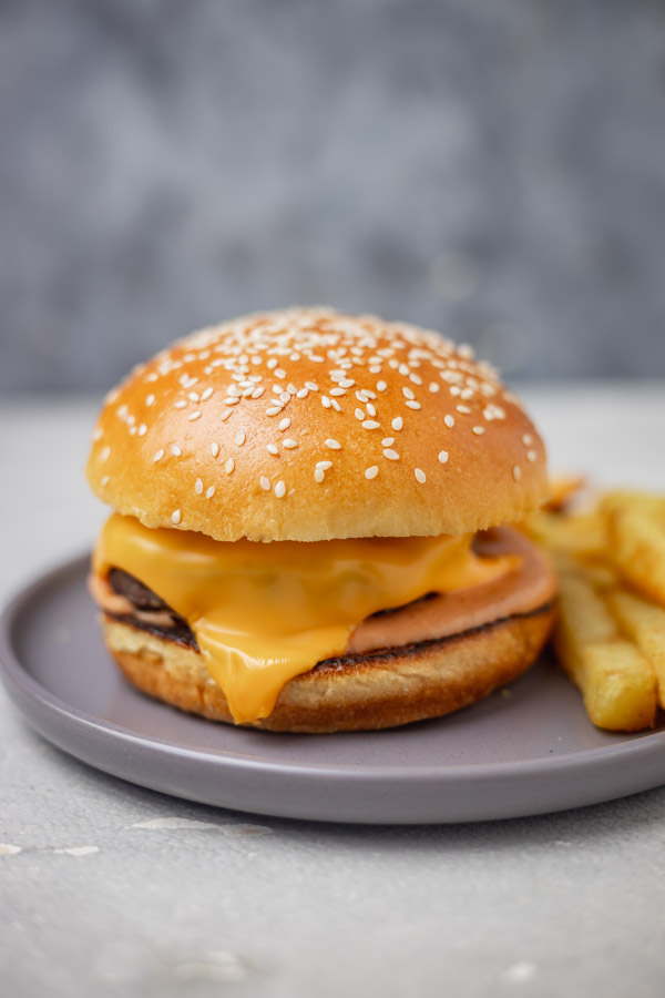 cheese beef burger on a plate with chips.