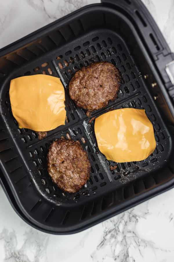 four cooked burger in the air fryer basket with two covered with cheese slices.