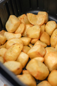 golden and crispy roast potatoes in the air fryer basket.