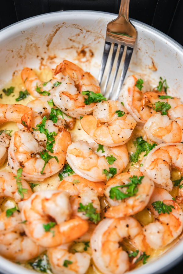 a silver fork pushing cooked shrimps in a white baking dish.
