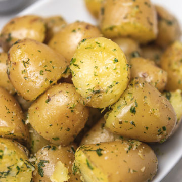 herby and buttery boiled potatoes on a plate.