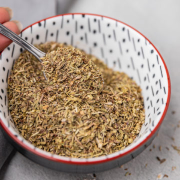a hand scooping dried herbs from a small patterned bowl.