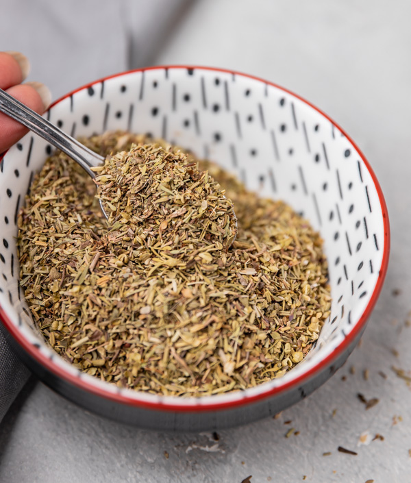 a hand scooping dried herbs from a bowl with a tea spoon.