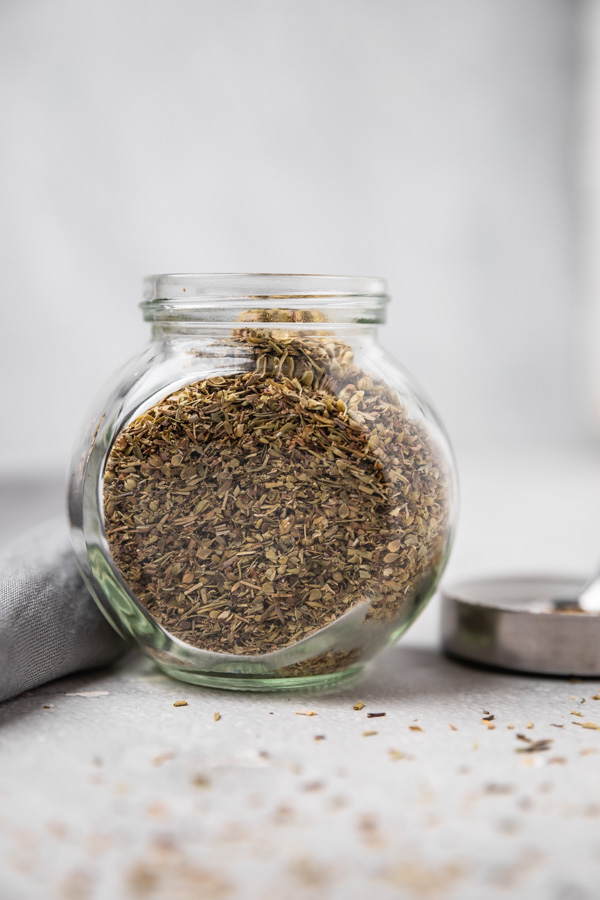 dried herbs spice in a spice jar placed beside a grey napkin