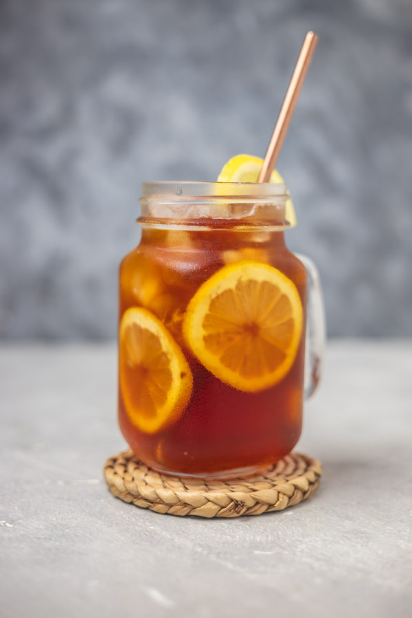 a glass of iced tea with straw placed on a woven coaster.
