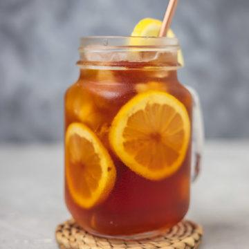 a glass of iced lemon tea with a straw.