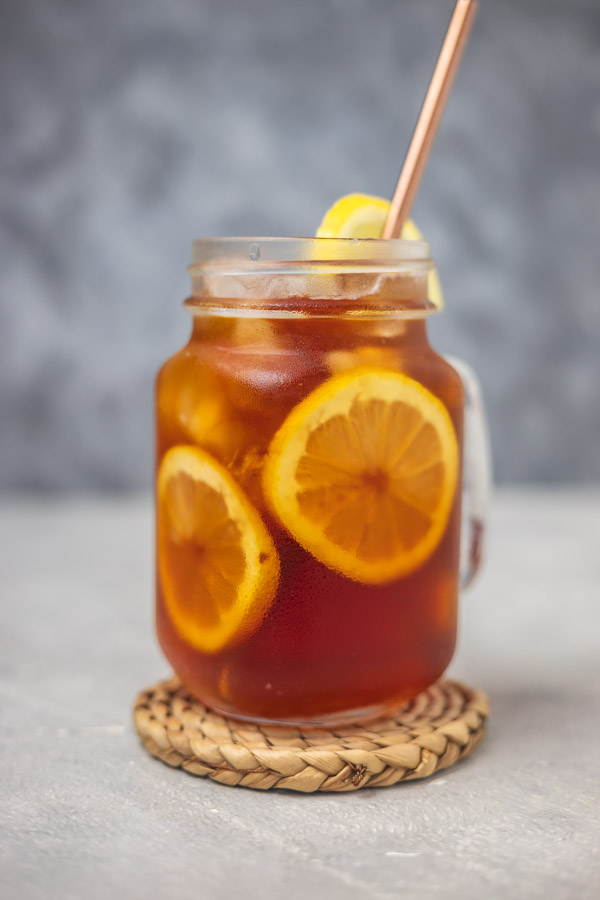 iced beverage garnished with lemon slices placed on a woven coaster.