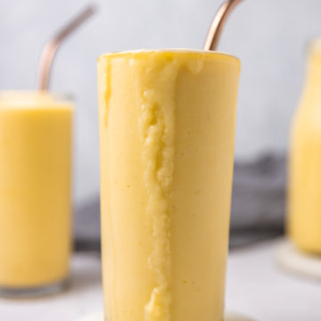 two glasses of mango pineapple smoothie with metal straws.
