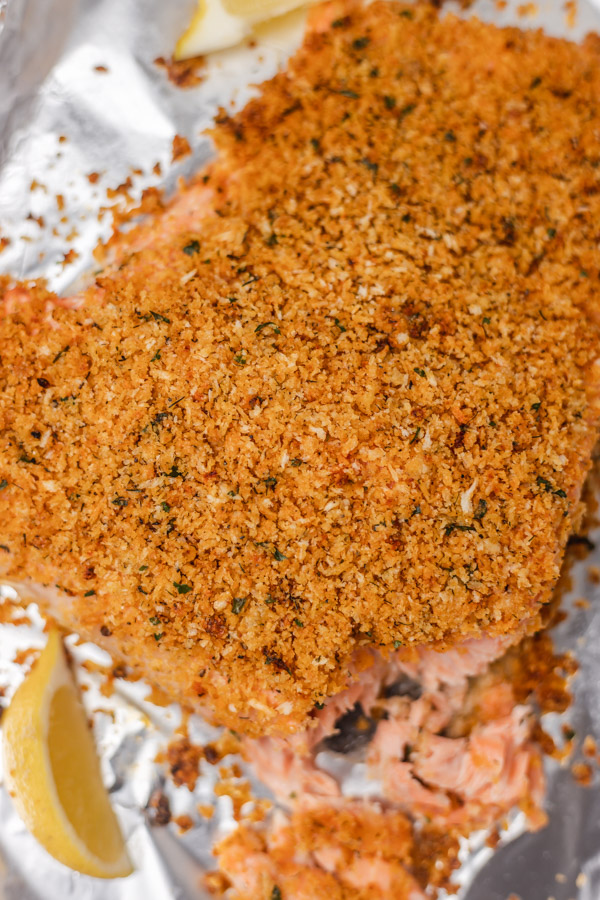a side of baked crusted salmon on a lined baking tray with a wedge of lemon.