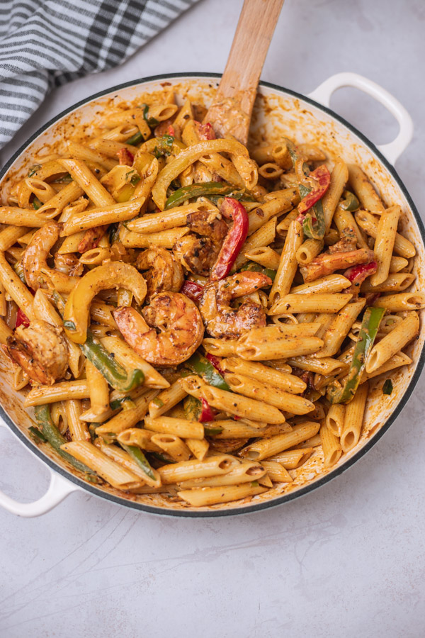 colourful shrimp pasta with bell peppers in a cast iron enamel pan.
