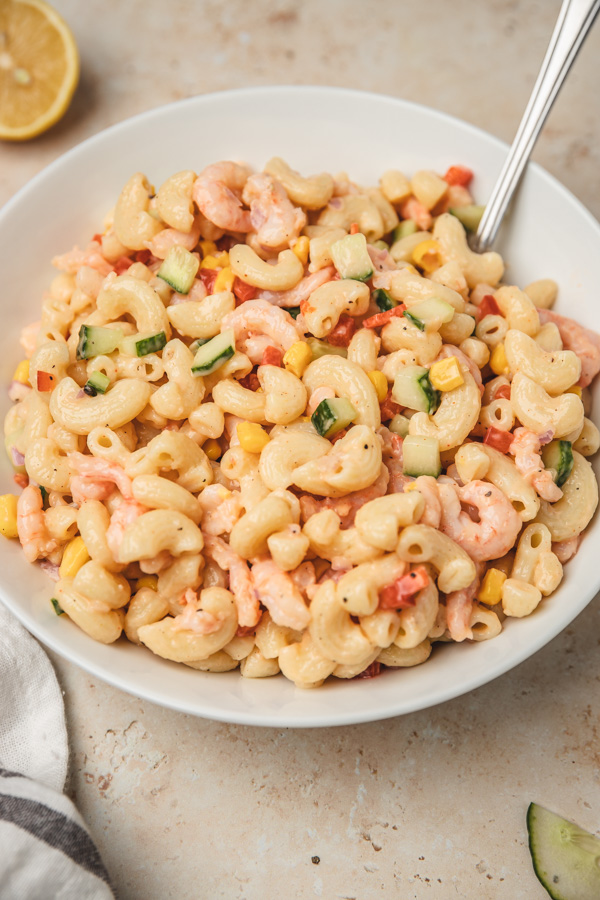 pasta salad in a white bowl with a spoon placed beside a white and grey napkin.
