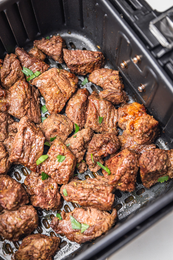 freshly cooked steak bites garnished with chopped parsley in an air fryer basket.
