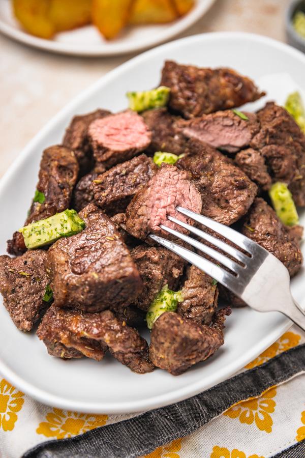 a platter of steak bites with a fork.