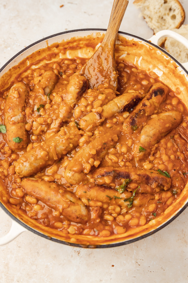 a casserole pan of baked beans casserole with a ustic bread on the side of the pan.