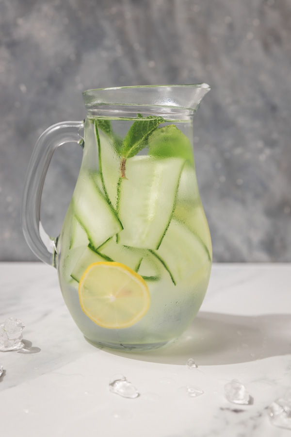 a pitcher filled with water, cucumber ribbon and lemon slices.