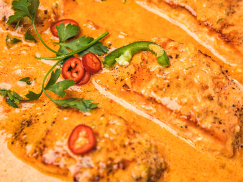 A close up shot of salmon curry garnished with fresh chilies and parsley.