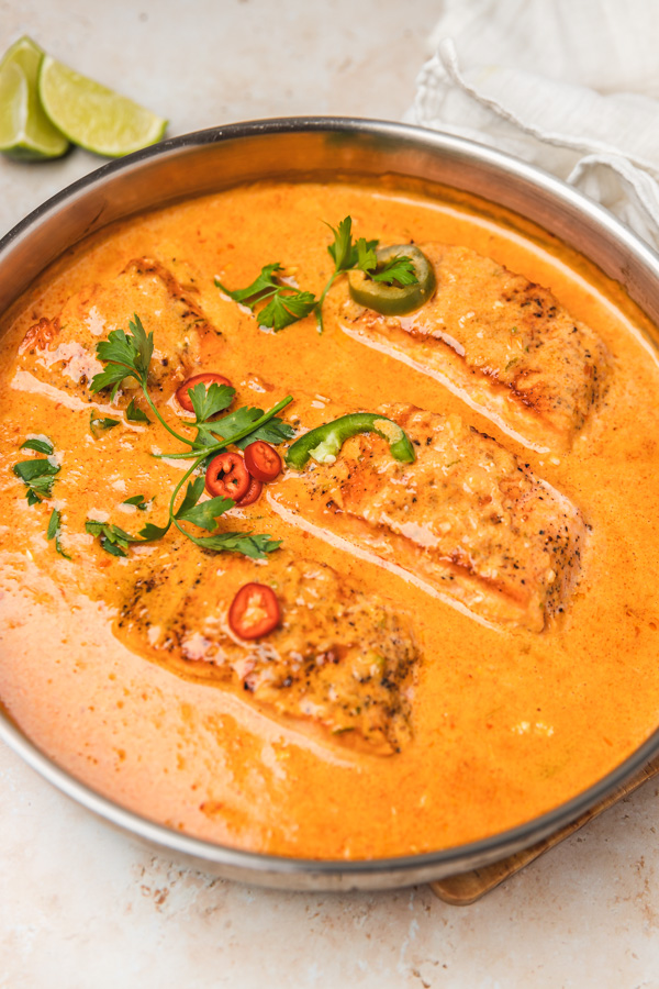 four salmon fillets in a pan of creamy coconut curry garnished with fresh chillies and parsley.