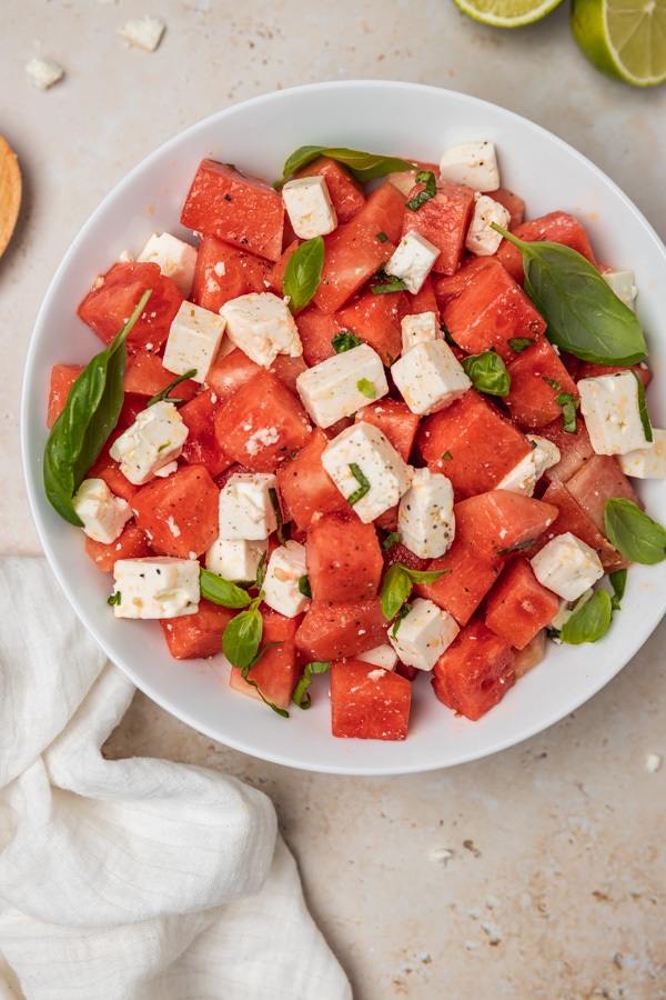 a bowl of fresh watermelon salad with cubed feta cheese and fresh basil.