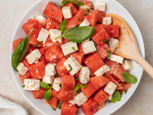 a bowl of watermelon feta salad with fresh basil and a wooden serving spoon.