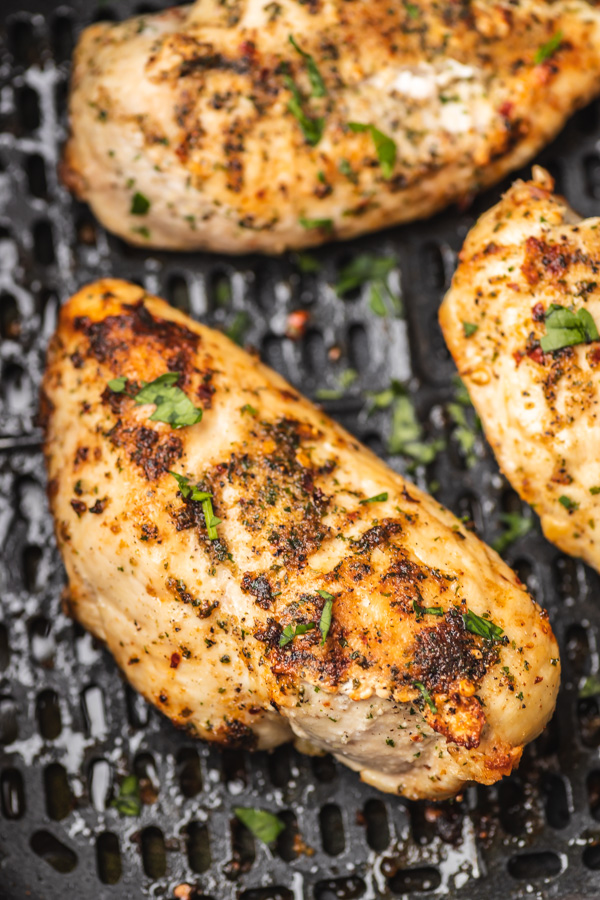a close up on cooked chicken in the air fryer.