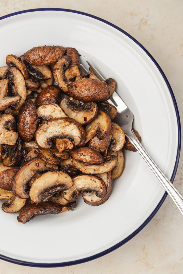 air fried mushrooms in a white enamel plate and fork.