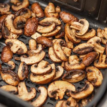cooked chestnut mushroom in an air fryer basket.