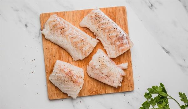 seasoned fish on a chopping board.